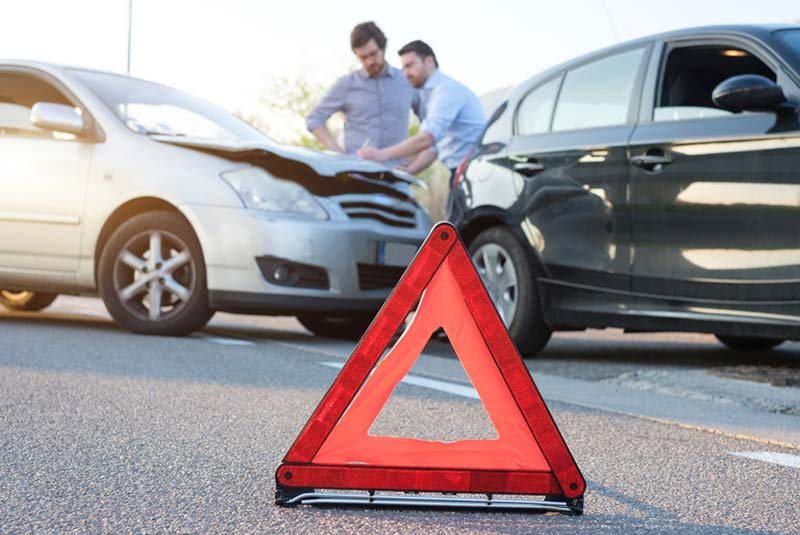 Reflective triangle on the road next to car accident